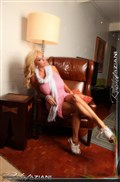 Rachel Aziani touches herself on a chair in a pink dress from Aziani