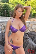 Sheila Grant poses outdoors in a shiny purple bikini from DDF Prod